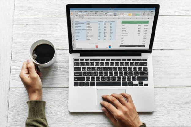 Person in front of laptop with excel display